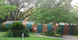 A modest Florida ranch house with dogwoods, oak trees, and a largec cycad in the yard. House is completely covered by a green and orange striped tent with a warning signed pinned near the front walkway indicating fumigation.
