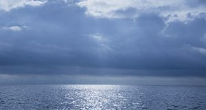 Photo of striking clouds over the Gulf of Mexico showing the horizon and rays of sun coming through the clouds turning the water silver.