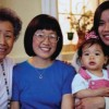 A family of four generations of women smiling for a picture.