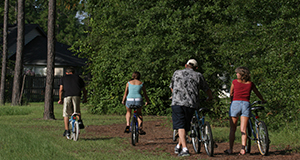 This image was taken prior to national guidelines of face coverings and social distancing. Family with bicycles.