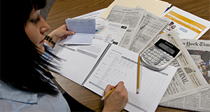 This image was taken prior to national guidelines of face coverings and social distancing. Person with a checkbook, calculator, and budgeting notebook.