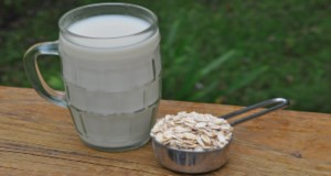 A mug of oat milk next to a small metal measuring cup brimming with oats, sitting on a wooden railing outside. Credit: Lincoln Zotarelli, UF/IFAS