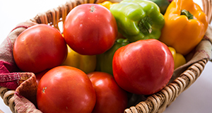Basket of fresh tomatoes and bell peppers.