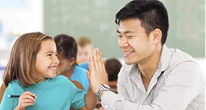 A photo of seated child and adult exchanging a high-five in an elementary school classroom.
